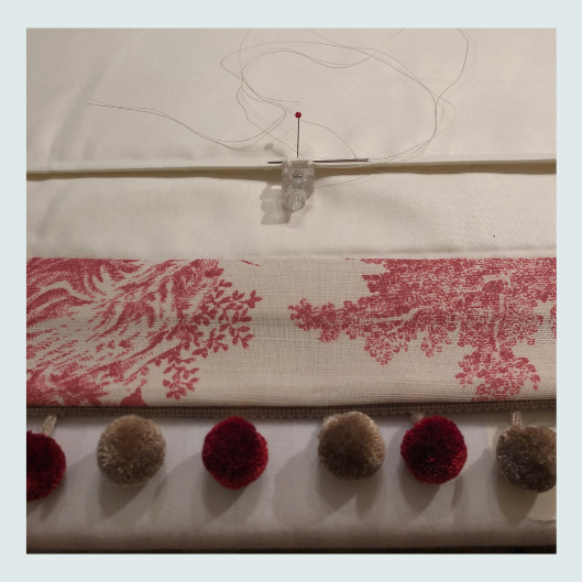 Work in progress, fixing a safety orb. Linen toile de jouy, bespoke handmade roman blinds with pom pom trim.