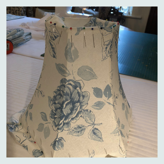 Stitching and pinning the face fabric onto a commissioned bespoke handmade tailored lampshade in blur and cream floral linen