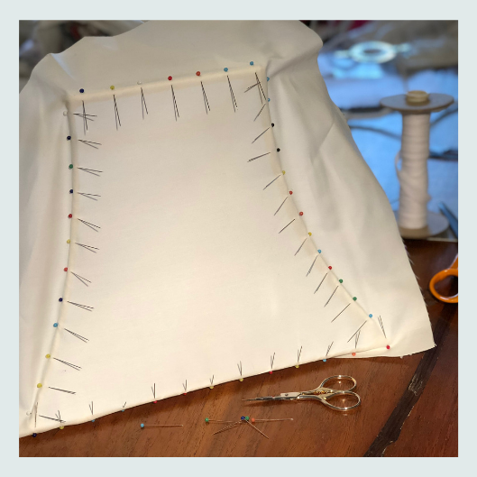 Pinning and stretching a pattern for a bespoke handmade tailored lampshade in William Morris strawberry thief design with a silk dupion contrast lining