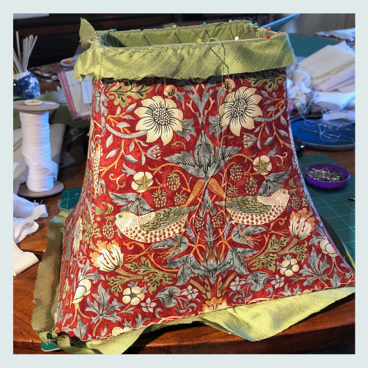 Final lampshade stitch for a bespoke handmade tailored lampshade in William Morris strawberry thief design with a silk dupion contrast lining