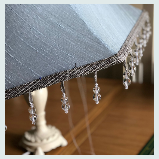 Hand sewing a beaded trim onto the base of a commissioned bespoke handmade tailored lampshade in wedgewood blue dupion silk