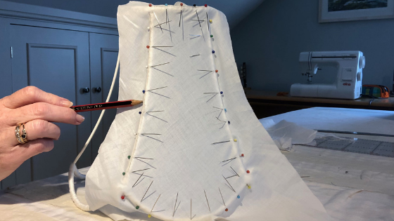 After pinning and stretching fabric taut on vintage lampshade use a soft pencil to make the outline alone the rings and struts to complete the template for a traditional handmade tailored lampshade